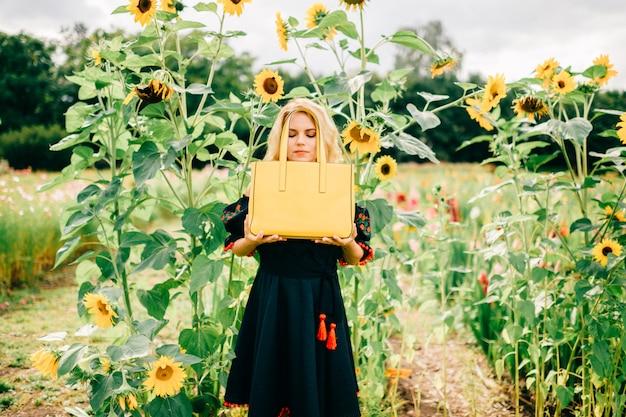 Levensstijlportret van ongebruikelijke blondevrouw die in zwart borduurwerk met ornament gele leerzak in bloementuin houden.