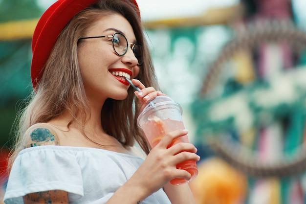 Levensstijlportret van vrij modieuze vrouw het drinken cocktail