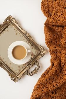 Levensstijlsamenstelling met kopje koffie met melk op vintage gouden dienblad en gebreide bruine deken plaid. plat leggen