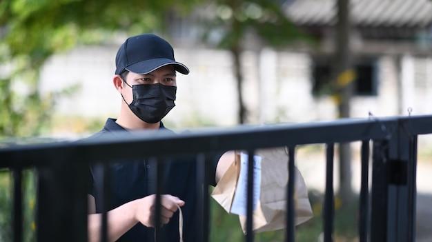 Lever de man in een beschermend masker met een papieren zak met eten en een wachtende klant bij de deuropening. maaltijdbezorgservice.