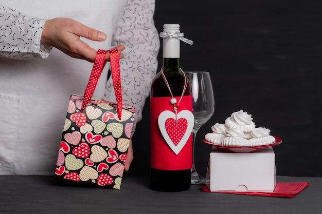 Lever een feestelijke tas in de buurt van een wijnfles met rood hart van valentijnsdag en gebak