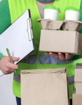 Lever in een groen vest met papieren dozen en een container om mee te nemen met twee witte kopjes koffie.