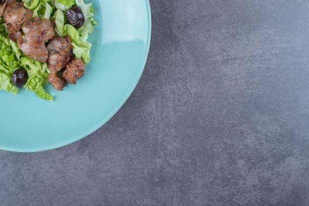 Lever kebab en olijven op blauw bord.