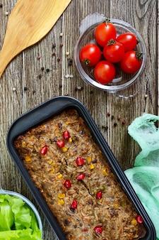 Lever ovenschotel. handig gerecht van de lever. vers gebakken varkensleversoufflé met rijst en groenten op een houten tafel. bovenaanzicht.