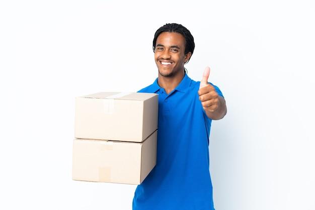 Levering african american man met vlechten geïsoleerd op een witte achtergrond met thumbs up omdat er iets goeds is gebeurd