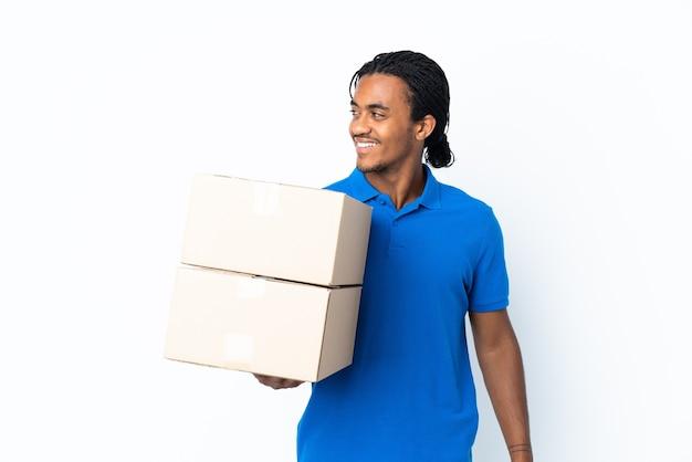Levering african american man met vlechten geïsoleerd op een witte achtergrond op zoek naar de zijkant en glimlachen
