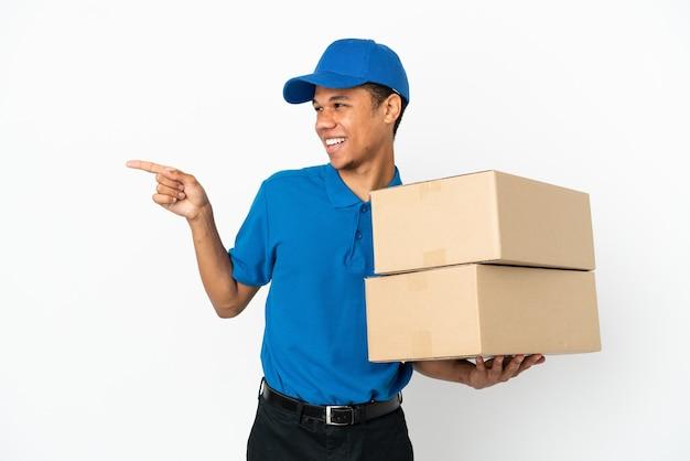 Levering afro-amerikaanse man geïsoleerd op een witte achtergrond die met de vinger naar de zijkant wijst en een product presenteert