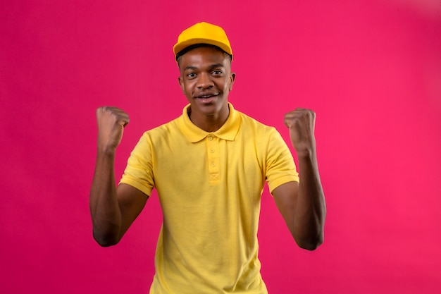 Levering afro-amerikaanse man in geel poloshirt en pet kijkt opgewonden verheugd over zijn succes en overwinning zijn vuisten balancerend van vreugde blij om zijn doel en doelen te bereiken staande op roze