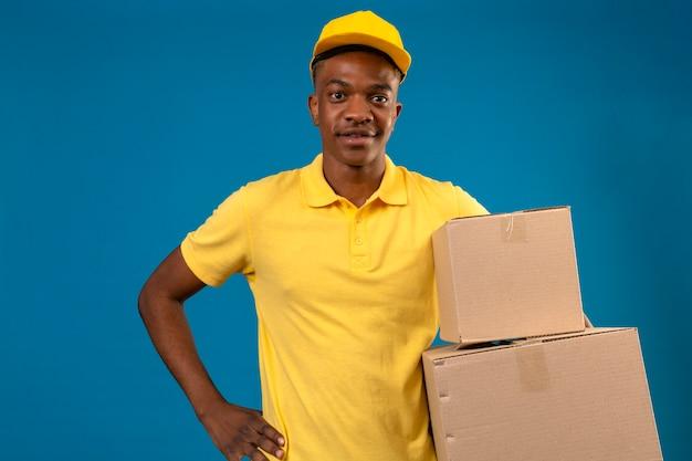 Levering afro-amerikaanse man in geel poloshirt en pet met kartonnen dozen met vriendelijke glimlach staande op geïsoleerde blauw