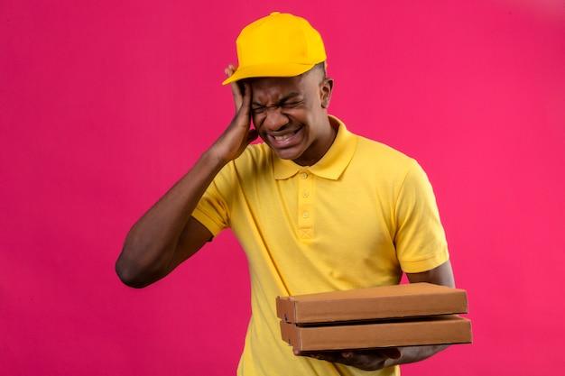 Levering afro-amerikaanse man in geel poloshirt en pet permanent met hand op het hoofd onwel lijdt aan sterke hoofdpijn op roze