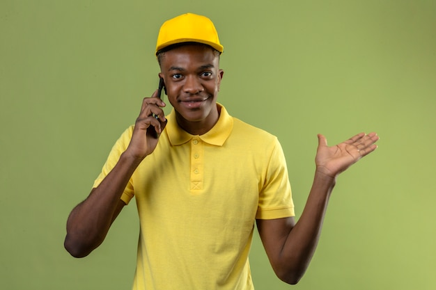 Levering afro-amerikaanse man in geel poloshirt en pet praten op mobiele telefoon glimlachend vriendelijk en presenteren en wijzen met handpalm staande op geïsoleerde groen