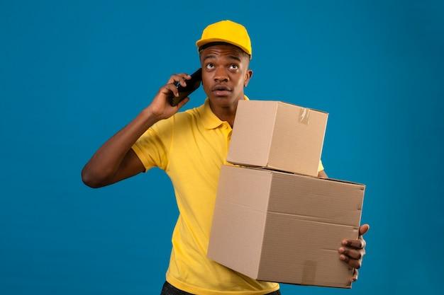 Levering afro-amerikaanse man in geel poloshirt en pet staan met kartonnen dozen praten op mobiele telefoon peinzende blik op geïsoleerde blauw opzoeken