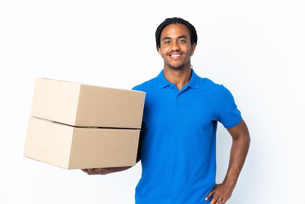 Levering afro-amerikaanse man met vlechten geïsoleerd op een witte achtergrond poseren met armen op heup en glimlachen