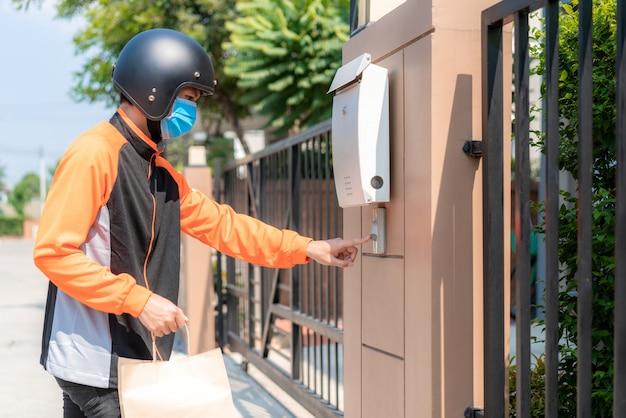Levering aziatische man draagt een beschermend masker in oranje uniform en klaar om te verzenden met een voedselzak voor de klant met koffers op de scooter,