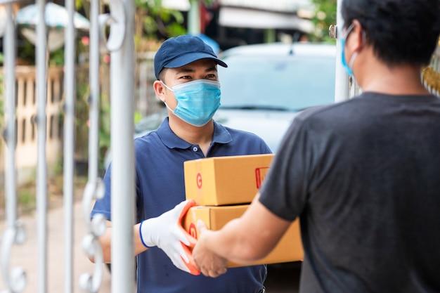 Levering aziatische man met kartonnen dozen in medische rubberen handschoenen en masker. online winkelen en expreslevering of e-commerce. concept voorkomen van de verspreiding van ziektekiemen en voorkomen van infecties covid-19