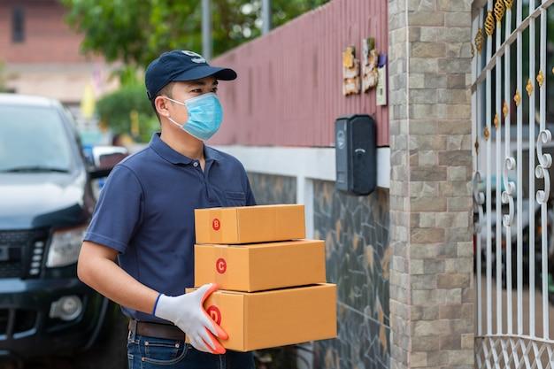 Levering aziatische man met kartonnen dozen in medische rubberen handschoenen en masker