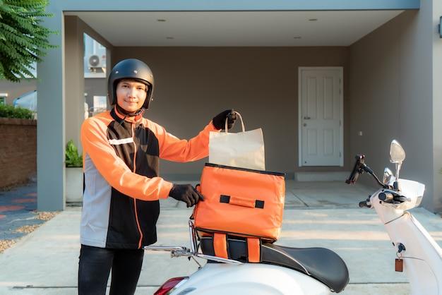 Levering aziatische man met oranje uniform en klaar om het verzenden van voedsel zak te sturen