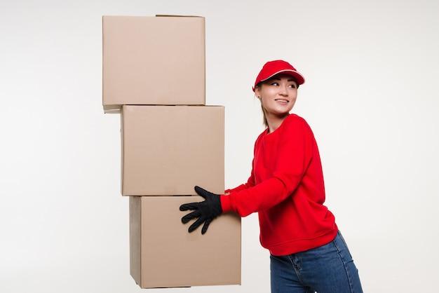 Levering aziatische vrouw in rood uniform geïsoleerd op witte muur vrouw in pet tshirt jeans werkt als koerier of dealer met kartonnen doos ontvangend pakket