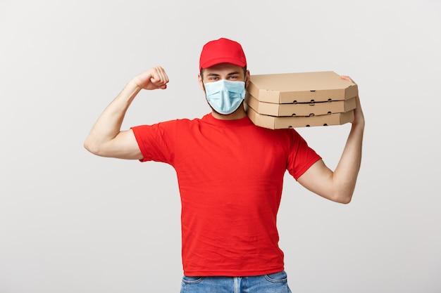 Levering concept - portret van sterke knappe bezorger buigen zijn spier en pizzadoos pakketten te houden.