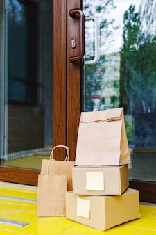 Levering dozen, papieren zakken voor de deur bij huisdeur. contactloze levering. veilig winkelen e-commerce aankooppakketten naar huis. dozen geleverd aan de voordeur. voorraad foto