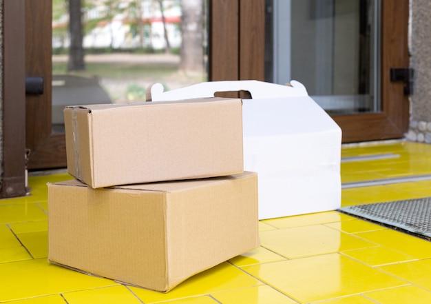 Levering dozen voor de deur thuis. contactloze levering van voedsel. veilig winkelen e-commerce aankooppakketten thuis