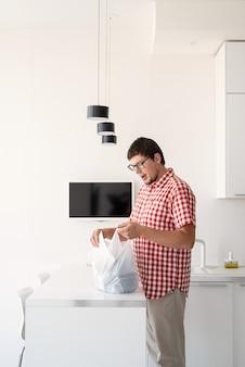 Levering eten, producten aan huis. winkelen en gezond voedsel concept. jonge man in rood geruit hemd met een wegwerp plastic zak met voedselbezorging in de moderne keuken