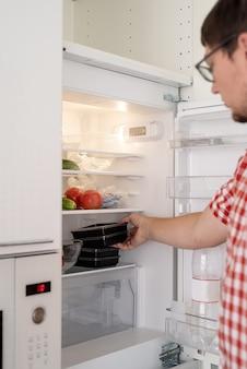Levering eten, producten aan huis. winkelen en gezond voedsel concept. jonge man in rood geruit hemd met wegwerpplastic in een doos met voedsel en zet ze in de koelkast