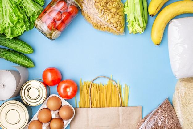 Levering eten. rijst, boekweit, pasta, ingeblikt voedsel, suiker, tomaten, komkommers, bananen op blauwe achtergrond.