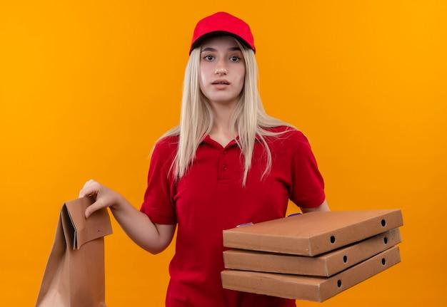 Levering jonge vrouw, gekleed in rode t-shirt en pet met papieren zak en pizzadoos op geïsoleerde oranje muur