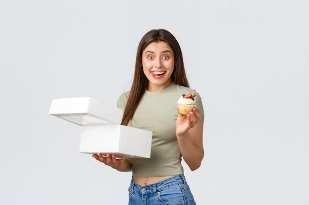 Levering, levensstijl en voedselconcept. opgewonden lachende jonge vrouw bestelde een doos met snoepjes uit het favoriete café of banketbakkerij, met een heerlijke cupcake, lik lippen van verlangen.
