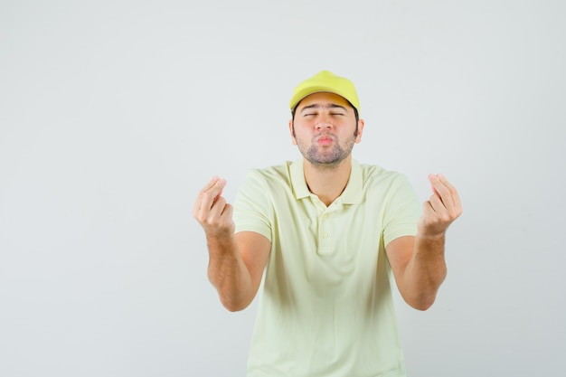 Levering man doet geld gebaar, lippen pruilen in geel uniform vooraanzicht.