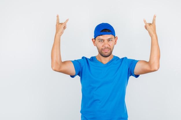 Levering man doet rock symbool in blauw t-shirt, pet en ziet er zelfverzekerd uit