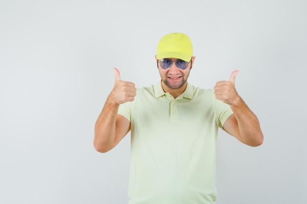 Levering man dubbele duimen opdagen in geel uniform en op zoek vrolijk. vooraanzicht.