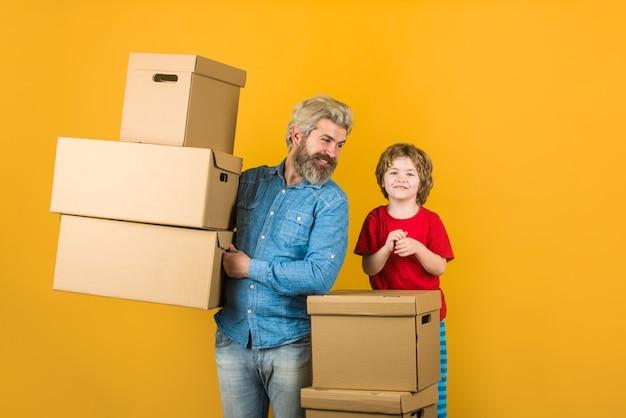 Levering. man en jongen met kartonnen dozen. gelukkige zoon en vader met kartonnen doos. internetaankopen en e-commerceconcept. leveringsconcept.