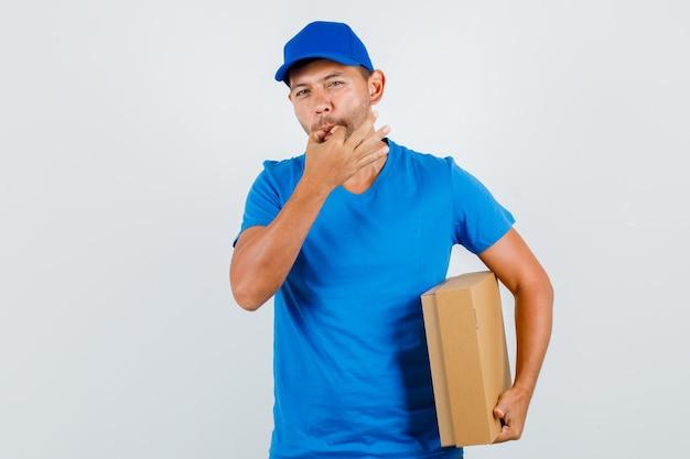 Levering man fluiten en kartonnen doos in blauw t-shirt te houden
