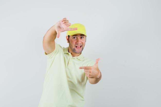 Levering man frame gebaar maken in geel uniform en op zoek vrolijk. vooraanzicht.