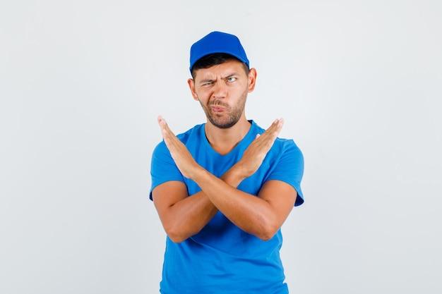 Levering man gebogen lippen met weigering gebaar in blauw t-shirt