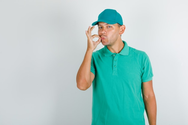 Levering man heerlijk gebaar maken in groen t-shirt met pet