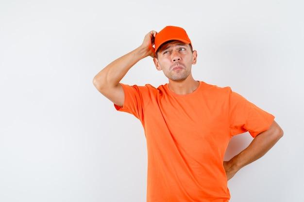 Levering man hoofd krabben in oranje t-shirt en pet en peinzend op zoek