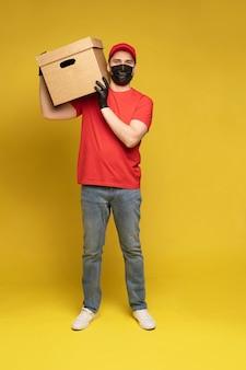 Levering man in beschermend masker en handschoenen met doos in studio geïsoleerd op gele muur