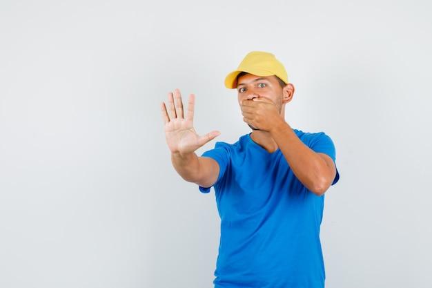Levering man in blauw t-shirt, pet met hand op mond zonder gebaar en bang op zoek