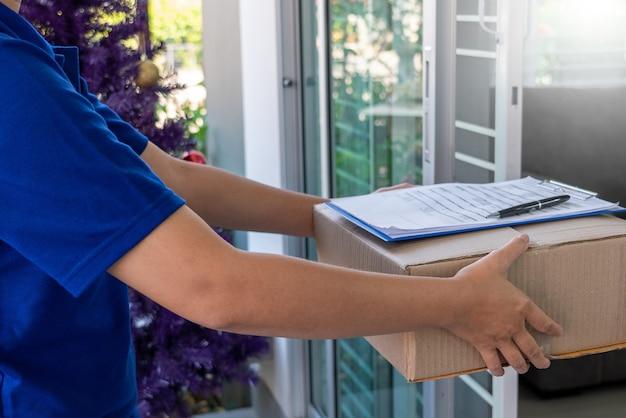 Levering man in blauw uniform overhandigen pakketdoos voor checklist voor ondertekening van de klant