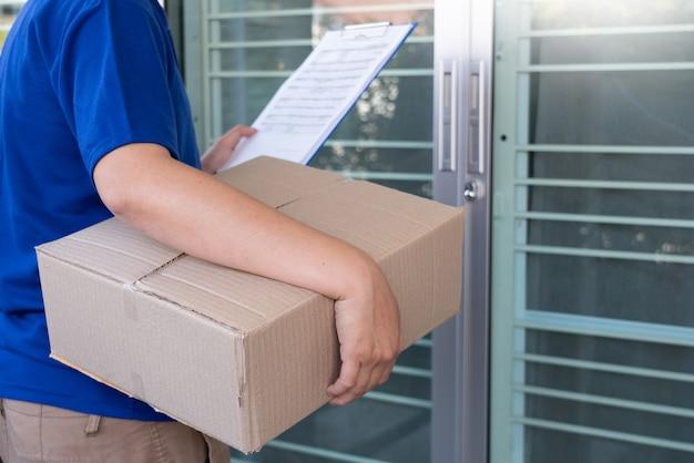 Levering man in blauw uniform pakketdoos overhandigen voor klant