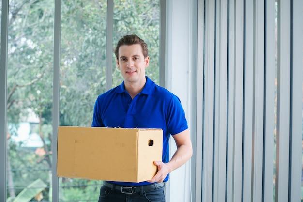 Levering man in blauw uniform van bezorgservice, online verkopen, e-commerce, verzending concept.
