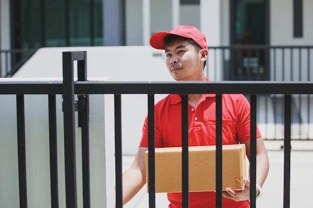 Levering man in een rode t-shirt met kartonnen doos