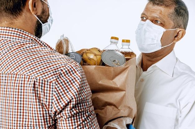 Levering man in gezichtsmasker en handschoenen. voedselbezorging, online winkelconcept terwijl coronavirus pandemie wereldwijd