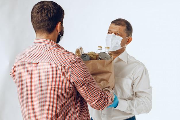Levering man in gezichtsmasker en handschoenen. voedselbezorging, online winkelconcept terwijl pandemie van het coronavirus