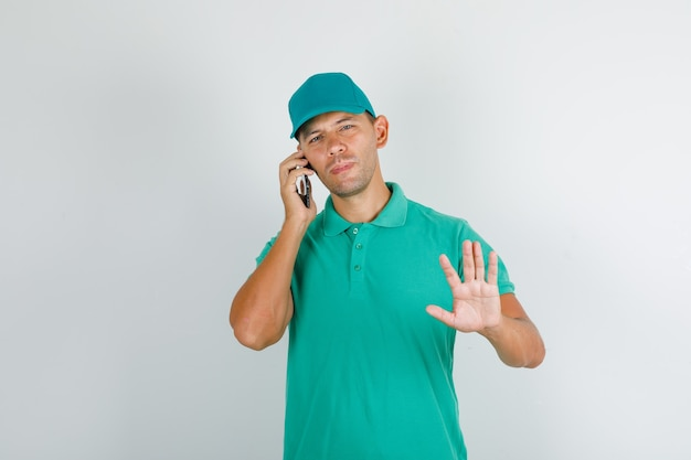 Levering man in groen t-shirt met pet praten over telefoon met stopbord