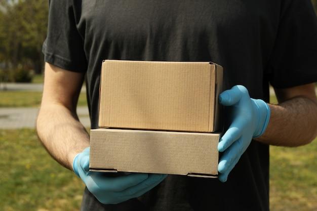 Levering man in handschoenen houdt lege dozen, ruimte voor tekst