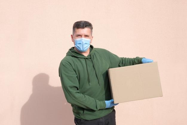 Levering man in medische masker en handschoenen houden en dragen van een kartonnen doos